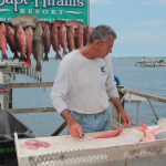 Captain Bruce filleting fish