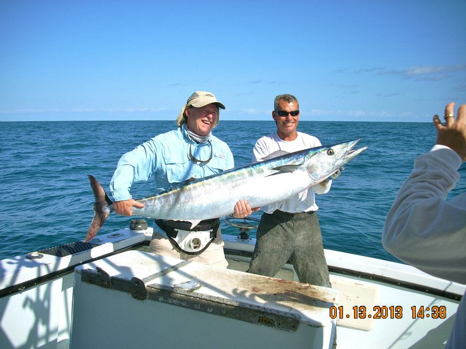 Captain Bruce holding a fish with client